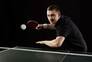 smiling tennis player in uniform playing table tennis isolated on black