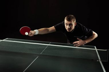 tennis player in uniform playing table tennis isolated on black