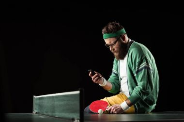 tennis player using smartphone while sitting on tennis table isolated on black