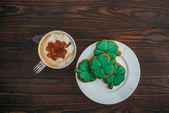 Fotografie top view of tasty cappuccino and cookies in shape of clovers on wooden table