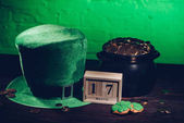 Fotografie calendar, cookies in shape of shamrock, green irish hat and pot with golden coins on wooden table