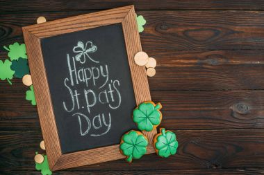 close-up view of wooden frame with happy st patricks day inscription and golden coins on table