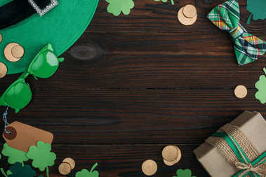 top view of golden coins, gift box and green accessories on wooden table