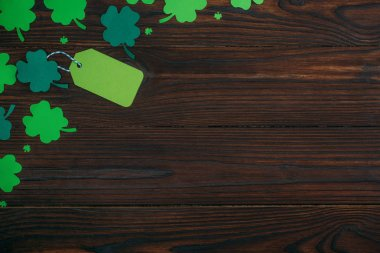 top view of blank green label and shamrocks on wooden table