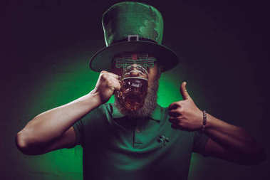 bearded man in green irish hat drinking beer and showing thumb up