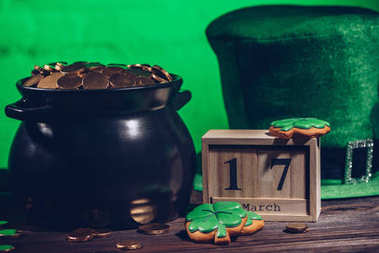 calendar, cookies in shape of shamrock, green irish hat and pot with golden coins, st patricks day concept
