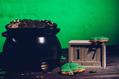 calendar, cookies in shape of shamrock and pot with golden coins on wooden table