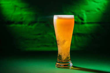 close-up view of glass with beer in green light, saint patricks day concept