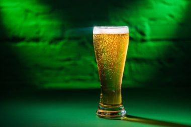 close-up view of glass with fresh cold beer in green light