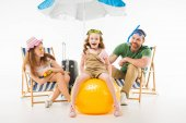 Happy little kid in swimming goggles sitting on ball between mother and father isolated on white, travel concept