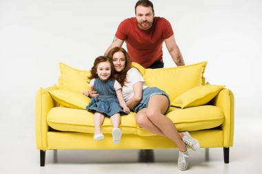 Happy family with sofa isolated on white