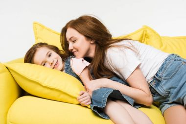 Smiling little kid with mother on couch isolated on white