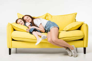 Happy mother and daughter on sofa isolated on white