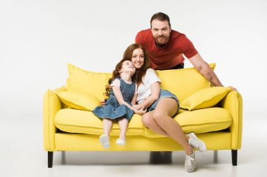 Mother and daughter on sofa while father standing behind isolated on white