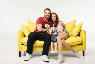 Happy family sitting on couch isolated on white