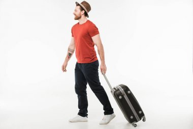 Stylish male tourist in hat carrying suitcase isolated on white, travel concept