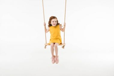 Little stylish child in dress riding on swing isolated on white