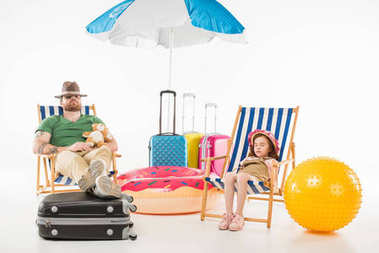 Father and daughter in hats sleeping in sun loungers isolated on white, travel concept