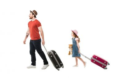 Father and daughter in hats carying suitcases isolated on white, travel concept