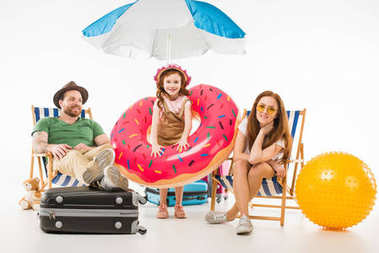 Little daughter with flotation ring standing between parents sitting on sun loungers isolated on white, travel concept
