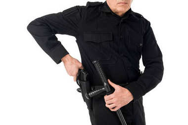 Close-up view of policeman in uniform pulling out gun isolated on white