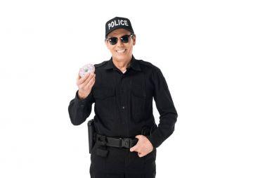 Smiling policeman holding doughnut isolated on white