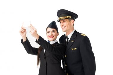 Airline captain and stewardess taking selfie isolated on white