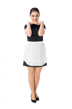 Smiling maid in professional uniform with hands by face isolated on white