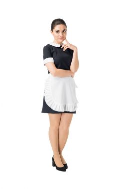 Brunette maid in professional uniform with hand by face isolated on white