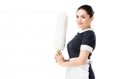 Smiling maid in uniform holding duster isolated on white
