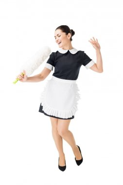 Professional maid in uniform having fun and singing in duster isolated on white