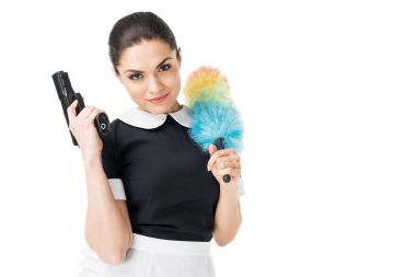 Brunette maid in professional uniform holding duster and gun isolated on white