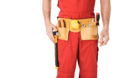 Close-up view of builder with tools in belt isolated on white