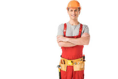 Cheerful construction worker in uniform with folded arms isolated on white