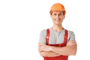 Smiling handyman in overalls with folded arms isolated on white