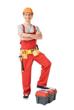Builder with tools in belt standing with folded arms isolated on white
