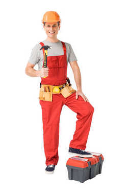 Cheerful construction worker holding hammer isolated on white