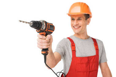 Smiling handyman in overalls holding drill isolated on white