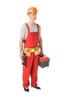 Professional builder in overalls and hardhat holding toolbox and drill isolated on white