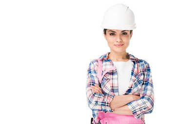 Smiling female construction worker in uniform with folded arms isolated on white