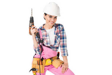 Smiling woman builder in overalls holding drill isolated on white