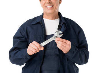 Cheerful plumber in uniform holding adjustable wrench isolated on white