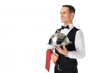 Smiling man in waiter uniform holding tray with cover isolated on white