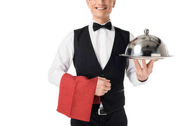 Smiling professional waiter presenting serving tray with cover isolated on white
