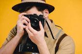 Fotografie mladý muž fotograf fotografování s fotoaparátem izolované na žluté