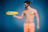 Fotografie junger Mann in kurzen Hosen und Tauchmaske mit Wasser Pistole auf blau