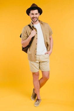 Full length view of handsome young man in shorts and hat holding backpack and smiling at camera isolated on yellow stock vector