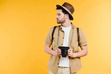 young man in hat with backpack holding camera and looking away isolated on yellow