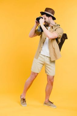 Full length view of smiling young man in shorts and hat photographing with camera isolated on yellow stock vector