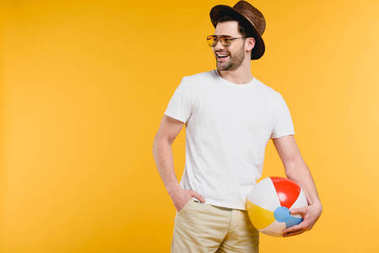 handsome smiling young man in hat and sunglasses holding inflatable ball and looking away isolated on yellow